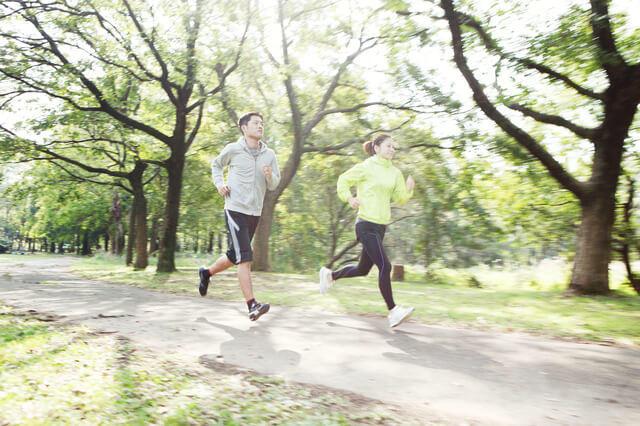 ジョギングをしている男女の写真。最大酸素摂取量は、個人が摂取できる単位時間当たりの酸素摂取量(l/分、あるいはml/kg/分)の最大値のことです。身体活動量を高め、全身持久力を図るための指標である最大酸素摂取量を高めることは、健康に生活できる健康寿命を延ばすことを示す。