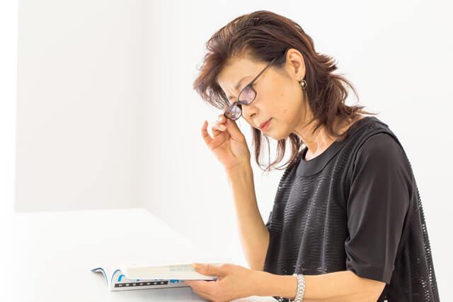 視力の低下に伴い眼鏡をかけて本を読む高齢女性の写真。老化現象の種類や始まる年齢は、個人差があり様々です。