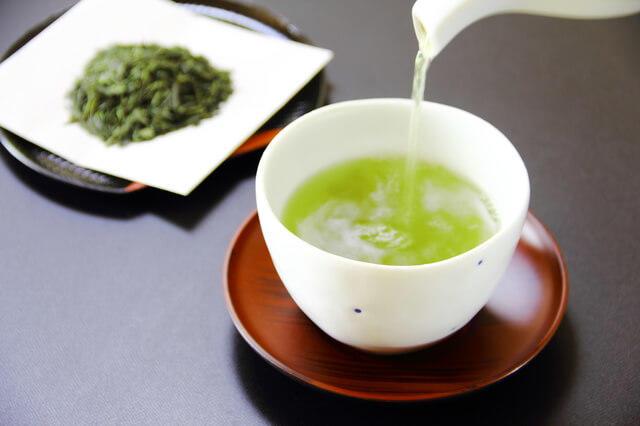茶葉と緑茶を入れる様子を表す写真。緑茶は玉露・煎茶・番茶・抹茶・ほうじ茶などの種類があります。ビタミンCの含有量が多いのが特徴です。抗酸化作用・体脂肪低下・リラックス作用などの効能効果が期待できます。